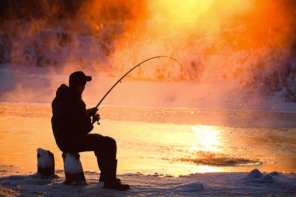 man fishing from bank in winter